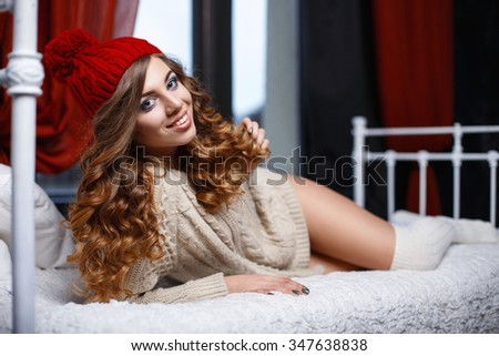 Beautiful happy girl in a knitted clothes lies on a bed