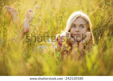 Beautiful happy girl in the grass looking up - stock photo