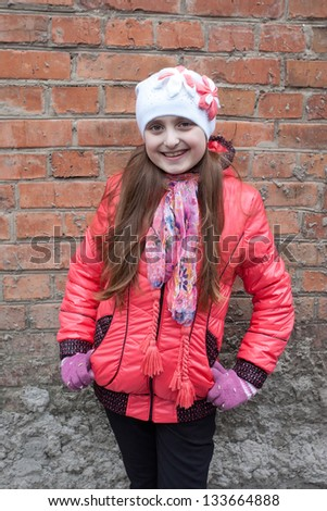 Beautiful happy girl in the red jacket - stock photo