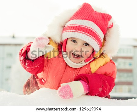 Beautiful happy girl in the red jacket winter outdoors. - stock photo