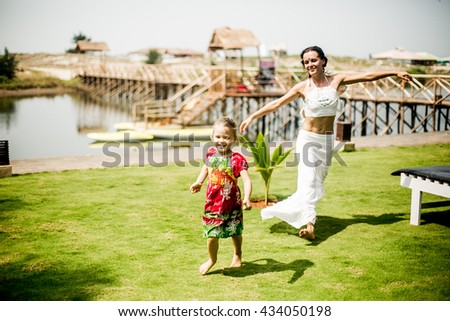 Beautiful happy girl on the back of her mother - stock photo