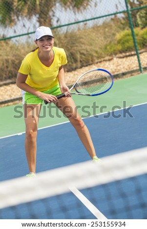 Beautiful happy girl or young woman laughing smiling and playing tennis - stock photo