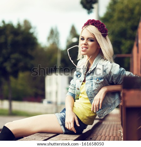 Beautiful happy girl relaxing outdoor. Pretty girl having fun sitting in row of  wood  seats at school stadium. Rest from study. Outdoors, Lifestyle - stock photo