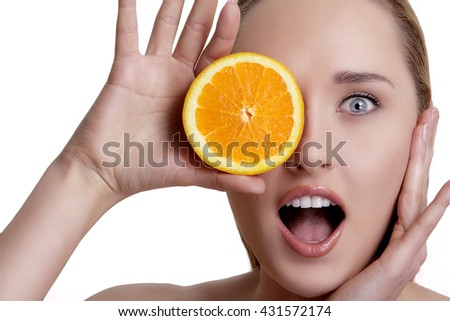 Beautiful happy girl showing a juicy orange on white