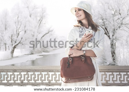 Beautiful happy girl with cell phone standing on the bridge on winter background - stock photo