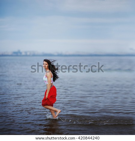 beautiful happy girl with long hair in a red skirt runs on water joyful and looking at camera - stock photo