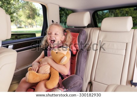 Beautiful happy girl with teddy bear sitting in the car - stock photo