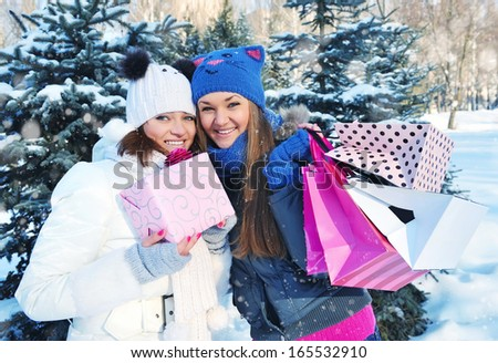 Beautiful happy girls with shopping bags in a winter park - stock photo