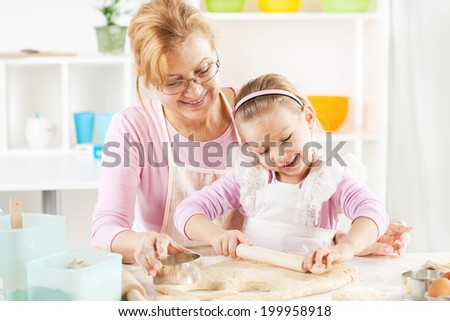 Beautiful happy grandmother and granddaughter a rolling pin together in the Kitchen.  - stock photo