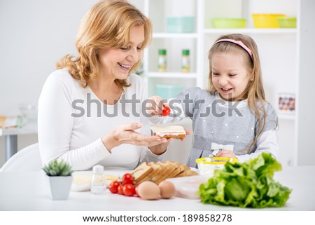 Beautiful happy grandmother and her cute granddaughter making Sandwich in the kitchen. - stock photo