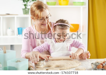 Beautiful happy grandmother learning her granddaughter to Baking in the kitchen. - stock photo