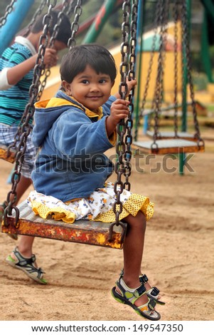 Beautiful &  happy indian girl ( child ) playing on a swing in a park. The photo shows summer time playground with a female kid smiling and sitting on a swing with a boy also playing in the background - stock photo