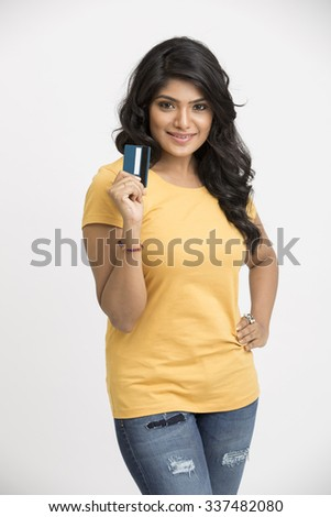 Beautiful happy Indian young girl with credit card on white.