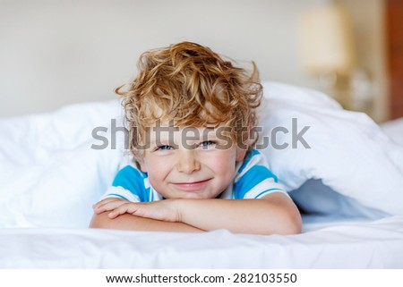 Beautiful happy kid boy after sleeping in his white bed. Little happy child smiling and laughing, indoors. - stock photo