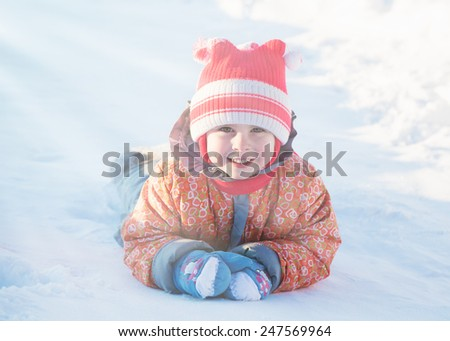 Beautiful happy kid in the  jacket in the winter outdoors.