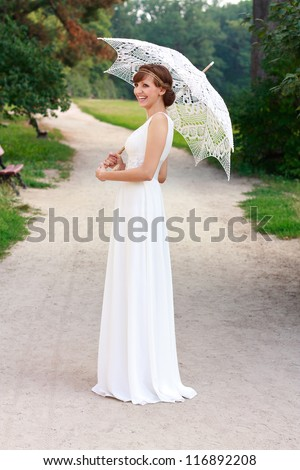 Beautiful happy laughing bride in white dress with decorative umbrella against background green nature. In a summer park