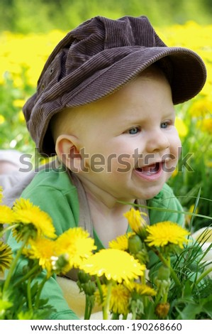 Beautiful happy little baby boy in hat sitting on a green meadow with yellow flowers dandelions on the nature in the park . Allergy concept - stock photo