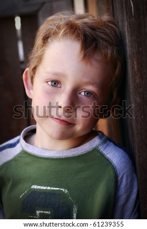 beautiful happy little boy leaning against a fence - stock photo