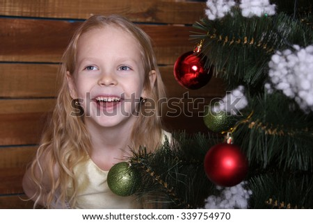 Beautiful happy little girl laughing near the Christmas tree.  - stock photo