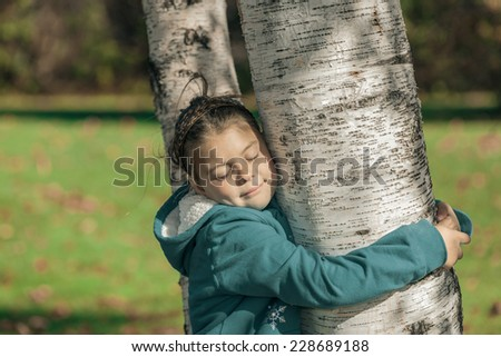 beautiful happy  little girl with closed eyes,  hugging a birch trees in autumn park and  enjoying her leisure time on sunny warm day  - stock photo