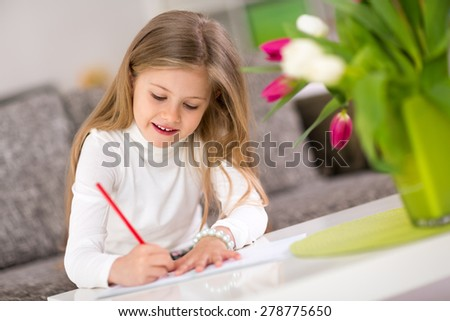 Beautiful happy little girl writing at home - stock photo