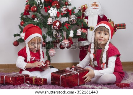 Beautiful happy little girls in red dresses are playing next to a Christmas tree, gifts and doll Santa's