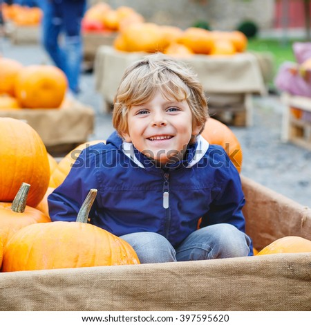 Beautiful happy little preschool kid boy on a pumpkin farm with huge vegetables. Child celebrating traditional festival halloween or thanksgiving. - stock photo