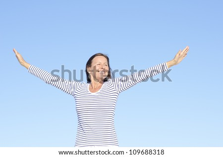 Beautiful happy looking mature woman in cheerful, positive, optimistic pose with arms up, isolated with blue sky as background and copy space. - stock photo