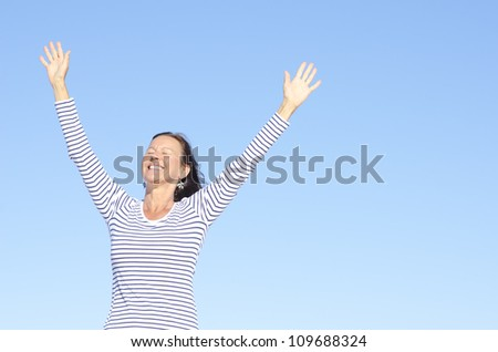 Beautiful happy looking mature woman in cheerful, positive, optimistic pose with arms up, isolated with blue sky as background and copy space.