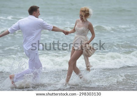 Beautiful happy lovely wedding couple of young paople holding hands standing in water on ocean beach coast and smiling, horizontal picture - stock photo