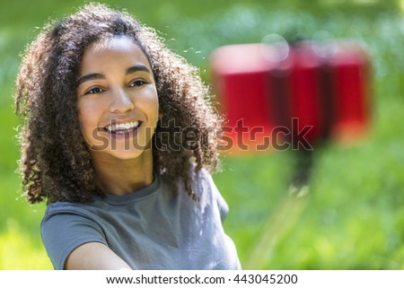 Beautiful happy mixed race African American young woman girl teenager female child smiling with perfect teeth taking selfie photograph with red cell phone on selfie stick - stock photo