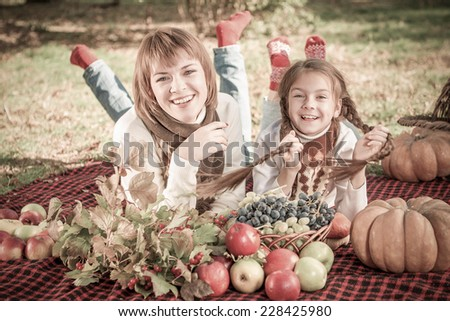 beautiful happy mother and daughter lying on a picnic. Autumn harvest. Apples, pumpkins, grapes, viburnum. - stock photo