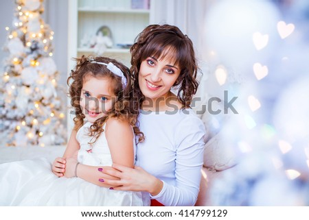 beautiful happy mother and daughter on the background of the christmas tree at home happy