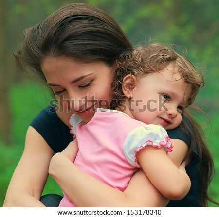 Beautiful happy mother hugging baby girl with love outdoors summer background. Closeup tender portrait - stock photo