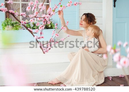 Beautiful happy mother with adorable daughter cute girl holding on hands and sitting on the porch near the blossom tree - stock photo
