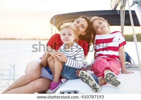 Beautiful happy mother with two daughters having great time at the yacht at summertime. Travel and vacation concept
