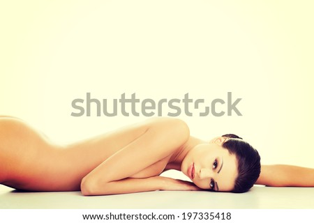 Beautiful happy  naked woman with fresh clean skin lying on belly - stock photo