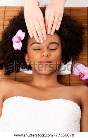 Beautiful happy peaceful sleeping Brazilian woman at day spa, laying on bamboo massage table with head on pillow wearing a towel getting a facial massage. - stock photo