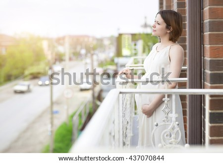 Beautiful happy pregnant woman on the balcony