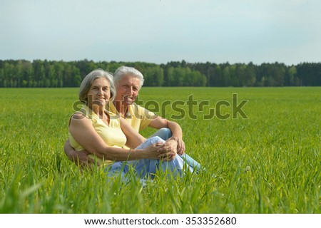 Beautiful happy senior couple have fun in summer field