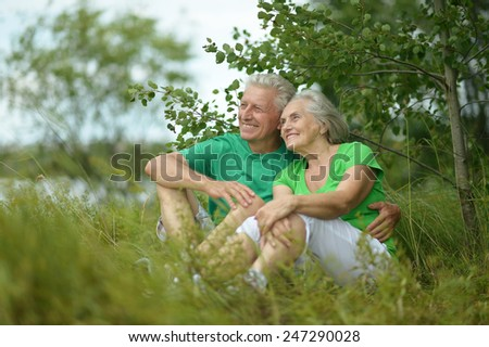 Beautiful happy senior couple in summer field