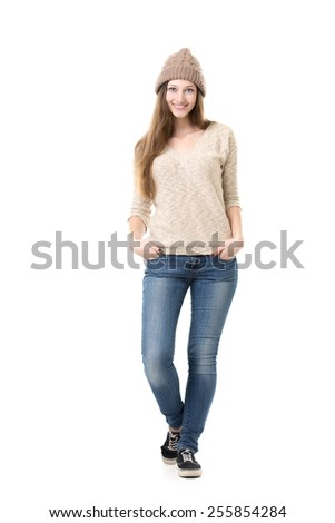 Beautiful happy shy smiling teenage girl posing in casual clothes, trying on new outfit - beige knitted hat, jersey, jeans and sneakers, isolated - stock photo