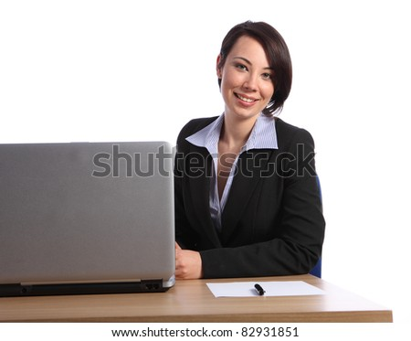 Beautiful happy smile by young business woman in office sitting to her desk with pen and paper next to laptop. She is wearing a black business suit.