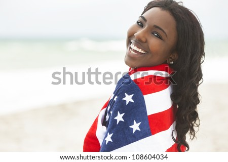 Beautiful happy smiling African American young woman or girl wrapped in American flag on a beach - stock photo