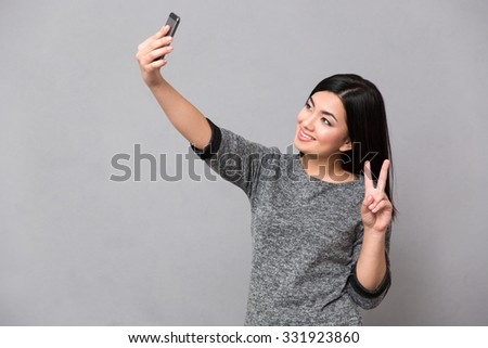 Beautiful happy smiling asian girl in gray jumper making selfie using cellphone and showing the peace sign with two fingers - stock photo