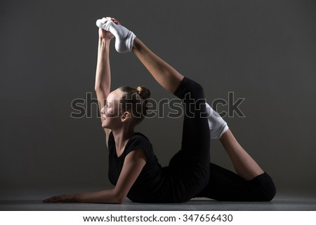 Beautiful happy smiling cool young fit gymnast athlete woman in sportswear doing art gymnastics, lying in one-legged bow posture, backbend acrobatic exercise, full length, studio, dark background - stock photo