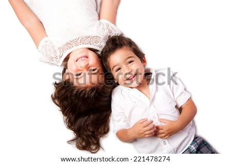 Beautiful happy smiling cute family siblings brother sister laying together on white. - stock photo