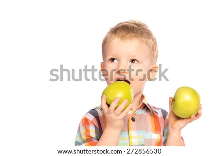 Beautiful happy smiling joyful child (little boy) eating healthy food (green apples)  isolated on white background. - stock photo