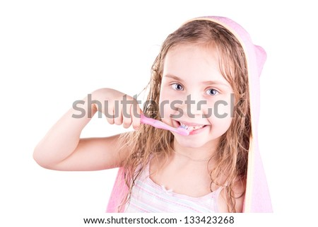 Beautiful happy smiling little girl brushing her teeth after bath, shower isolated on white