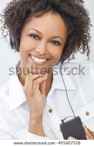 Beautiful happy smiling mixed race African American girl or young woman wearing a white shirt listening to music on mp3 player and headphones